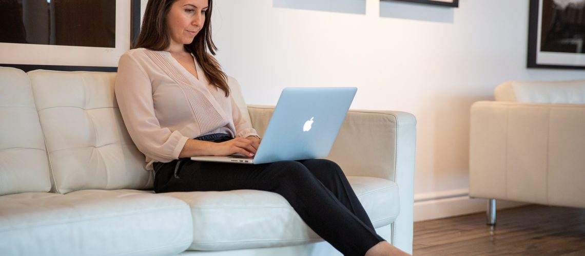 Woman sitting on a white couch with laptop on her lap