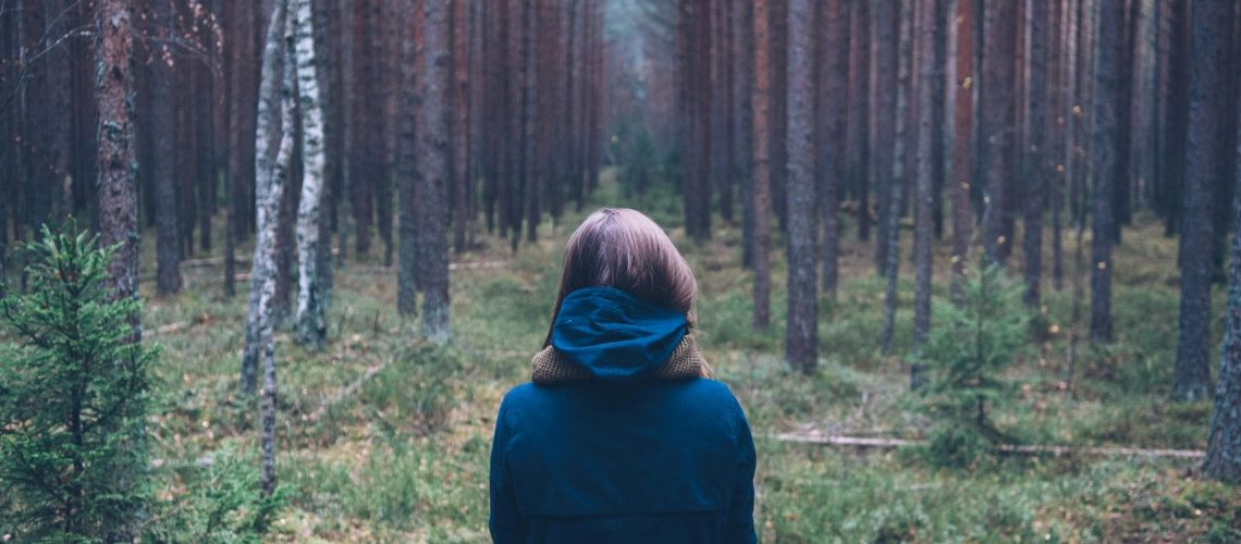 girl standing in forest alone