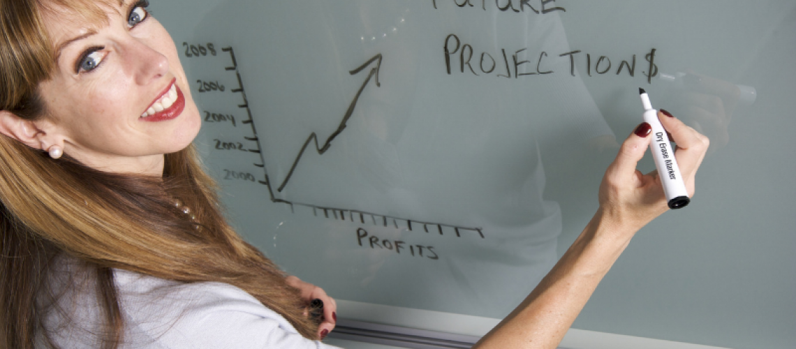 woman with white shirt writing future projections on white board looking at camera